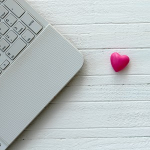 Lap top computer and heart on wooden white table - love technology concept